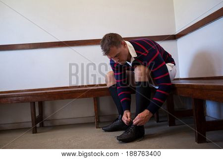 Rugby player tying shoes while sitting on bench against wall in locker room
