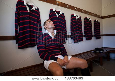 Tired player wearing jersey sitting on bench against wall in locker room