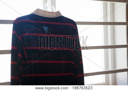 Close-up of rugby shirt hanging on window during sunny day