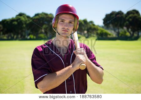 Portrait of young baseball player holding bat while standing on field