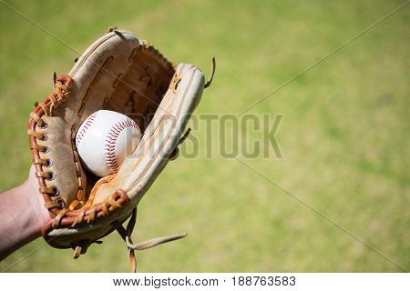 Cropped hand of baseball pitcher holding ball in glove at field