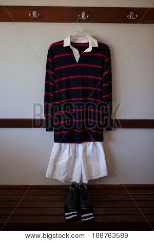 Rugby uniform hanging over shoes and socks on wooden bench in locker room