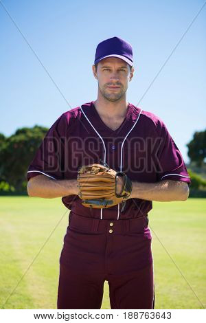 Portrait of confident baseball pitcher standing on field against clear blue sky
