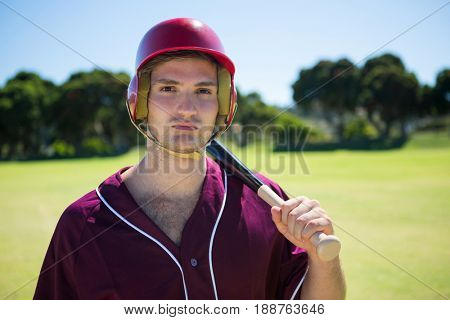 Portrait of young player holding baseball bat while standing on field