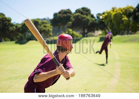 Baseball players playing together on field during sunny day