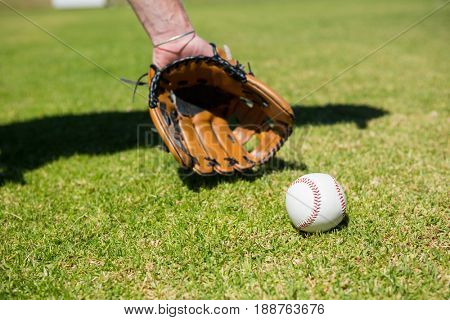 Cropped hand of baseball pitcher by ball on playing field