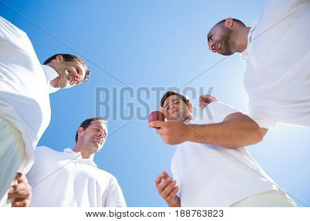 Low angle view of cricket team standing on field against clear sky