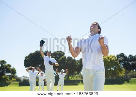 Happy cricket team enjoying victory while standing on field against clear sky