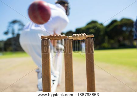 Close up of ball by stump against batsman on field