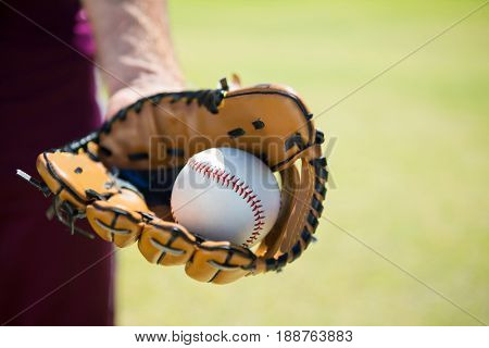 Cropped image of baseball pitcher holding ball on glove at playing field