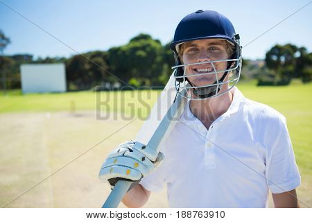 Portrait of smiling cricket player holding bat while wearing helmet at field on sunny day