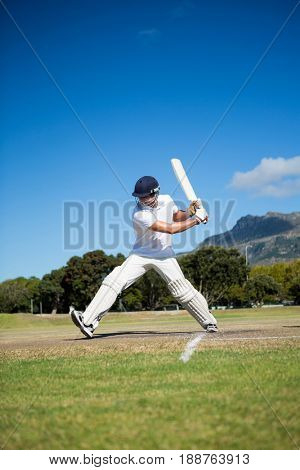 Full length of batsman playing at field against sky on sunny day