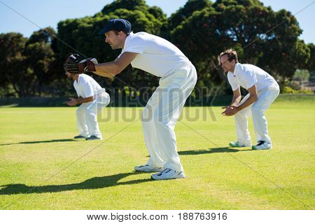 Side view of players bending while playing cricket at field on sunny day
