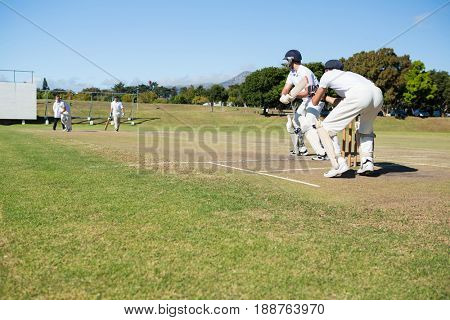 Cricket players playing match at field on sunny day