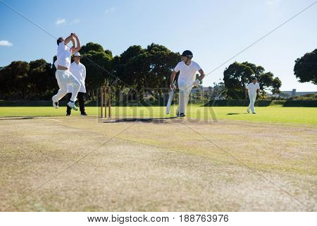Players playing cricket match at field on sunny day
