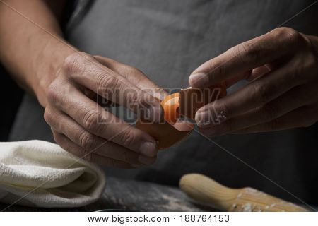 closeup of a young caucasian man separating the yolk of an egg using the broken shell, on a rustic wooden table next to a rolling pin