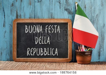 the text buonna festa della repubblica, happy republic day, the national day of italy, written in italian in a chalkboard, and a flag of italy, on a rustic wooden table