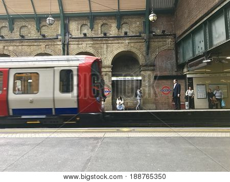 LONDON - MAY 16, 2017: Passengers wait to board as Tube train arrives at Notting Hill Gate station on the District and Circle Line of the London Underground in Notting Hill, West London, UK.