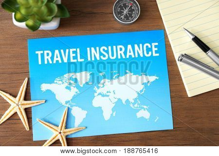 Picture with text TRAVEL INSURANCE on table, closeup