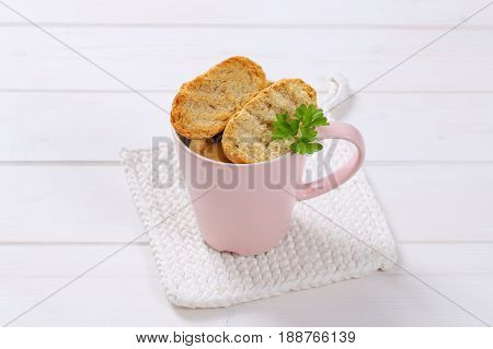 cup of crispy rusks on white table mat