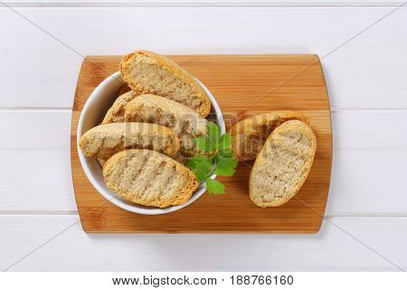 bowl of crispy rusks on wooden cutting board