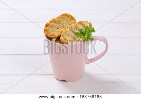 cup of crispy rusks on white wooden background