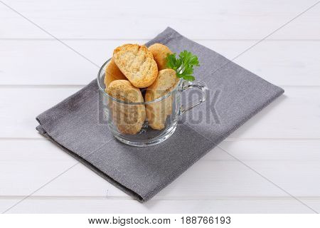 cup of crispy rusks on grey place mat