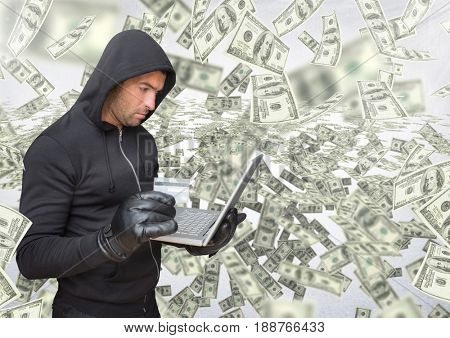 Digital composite of Criminal in hood on laptop in front of lots of money