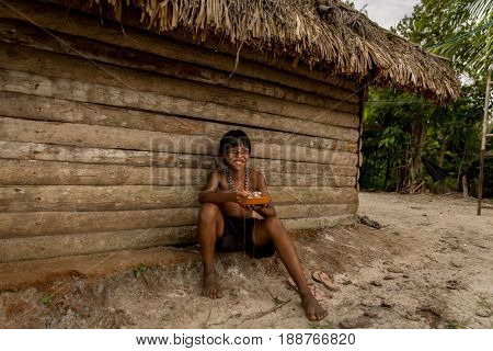 Native Brazilian child eating food at Tupi Guarani Tribe
