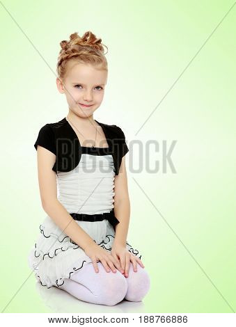 Beautiful little blonde girl dressed in a white short dress with black sleeves and a black belt.Girl sitting on his lap putting his hands on them .