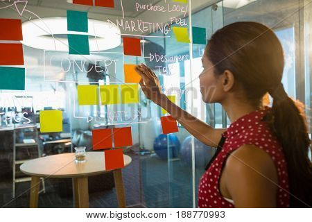 Female executive sticking notes on glass board in office