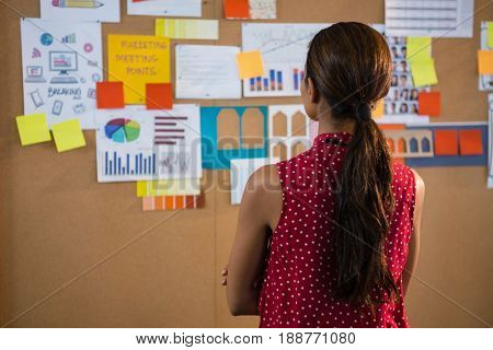 Rear view of female executive looking at the bulletin board in office