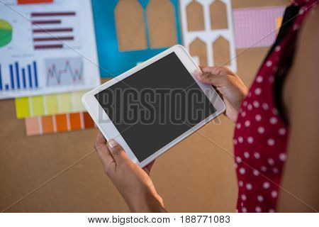 Mid-section of female executive using digital tablet near bulletin board in office