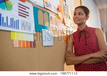 Female executive looking at graph on the bulletin board in office