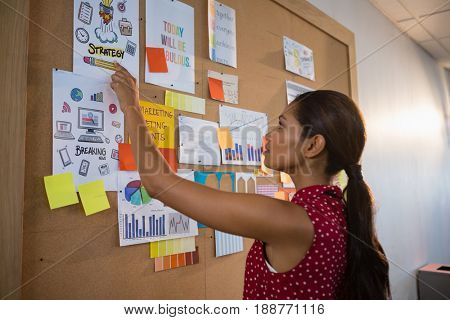 Female executive pointing the document on bulletin board in office