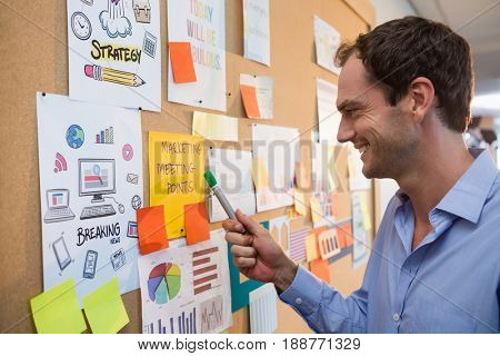 Male executive looking at bulletin board in office