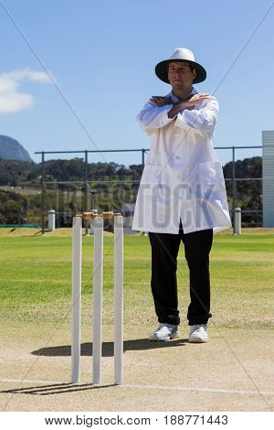 Full length of cricket umpire signaling cancel call sign during match against blue sky on sunny day