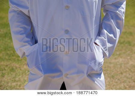 Mid section of cricket umpire standing with hands in pockets on field