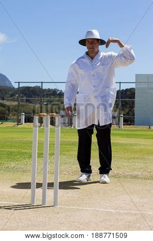 Cricket umpire signaling one short sign during match against blue sky on sunny day