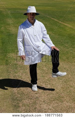 Portrait of cricket umpire signaling leg bye on field during match