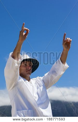 Low angle view of cricket umpire signalling six runs against blue sky during match on sunny day