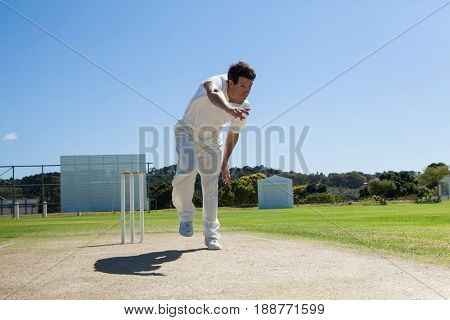 Bowler delivering ball during cricket match against clear blue sky on sunny day