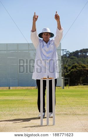 Cricket umpire signalling six runs during match on sunny day against clear sky