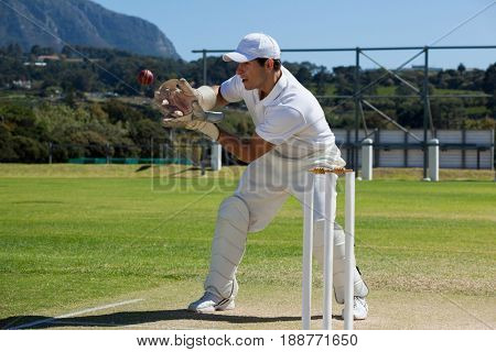 Full length of wicketkeeper catching cricket ball behind stumps on field during sunny day