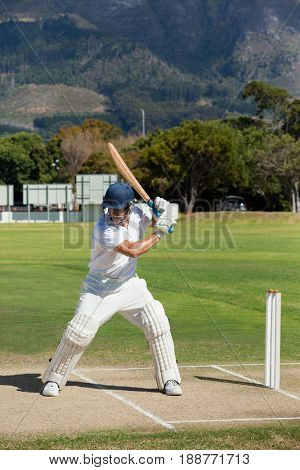 Cricket player practicing on field during sunny day