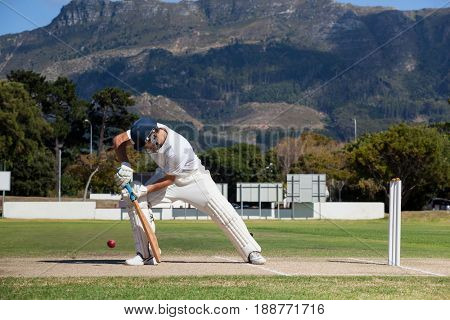 Full length of batsman playing cricket on field against mountain during sunny day