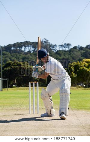 Cricket player playing on field against clear sky during sunny day