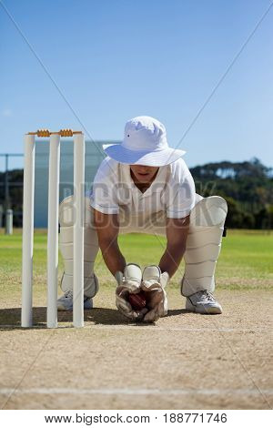 Full length of wicketkeeper holding ball behind stumps against blue sky on sunny day