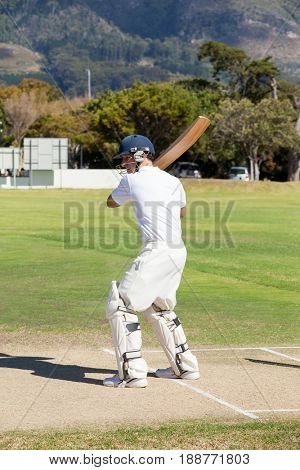 Batsman playing cricket on field during sunny day