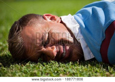 Close up of injured rugby player lying on playing field